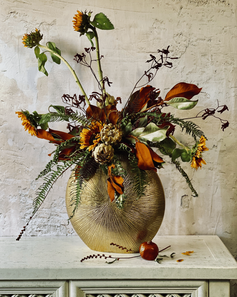 Flower arrangement featured in this article featuring russet sunflowers, dried artichokes, dried magnolia, dried kangaroo paw flowers